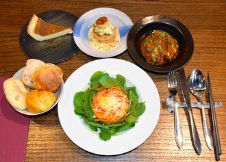 ランチのコース。右上から時計回りにメインの定番「豚バラ肉のトマト煮込み」、前菜のサラダ、パン、チーズケーキ、もう一つのメイン「白身魚のニョッキのパイ包み