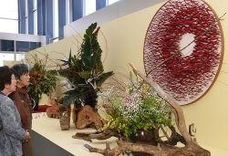 いけばなインターナショナルチャリティー花展で、個性あふれる作品に見入る来場者=28日、那覇市久茂地のタイムスビル