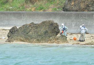 沿岸部の岩場にロープを巻き付ける作業員=13日午前11時、名護市辺野古・米軍キャンプ・シュワブ