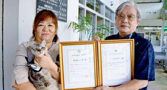 仲村正樹さん(右)から「『小さな親切』実行章」を受け取る知念花代子さんと猫の「もも」=沖縄市・諸見里自治会事務所