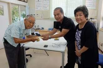 イモのお礼として寄付を手渡す安里祥徳さん(左)と受け取る安慶名会長(中央)、右は屋比久さん=田場公民館