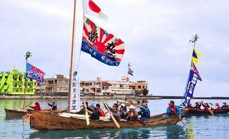大漁旗を掲げ、糸満漁港内をパレードする「帆掛サバニ漕ぎ初め会」の参加者たち=糸満