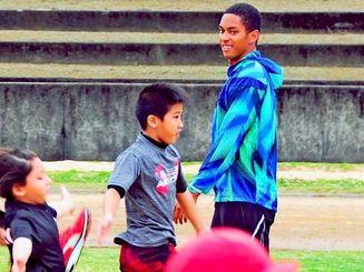 児童・生徒らに短距離のフォームを指導するケンブリッジ飛鳥さん(右)=18日、豊見城総合公園陸上競技場