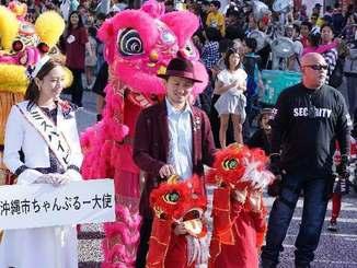パレードに参加するちゃんぶる~沖縄市大使のISSAさん(中央)=24日午後、沖縄市・コザゲート通り(下地広也撮影)