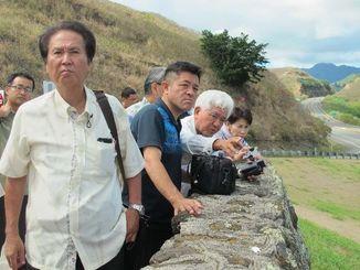 丘の上から米軍基地を視察する渡久地修沖縄県議(手前)ら=27日午前、米ハワイ州