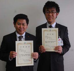 医療経営士2級を取得した呉屋氏(右)と昨年取得した伊波グループ長=29日、沖縄タイムス社