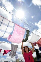 強い日差しと青空が広がり気持ちよく洗濯物を干す女性=22日午前、那覇市久茂地