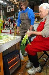 ストーブで足元を暖めながら島ラッキョウを束ねる市場の店員=午後4時49分、那覇市・牧志公設市場
