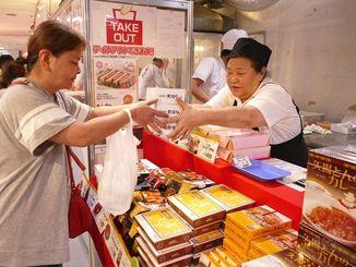 「三重と名古屋のうまいもの市」初出展の「矢場とん」で購入する客=5日、那覇市・デパートリウボウ