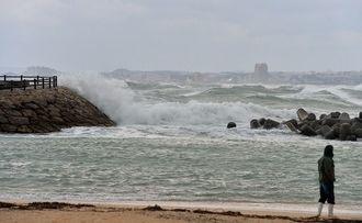 海は強風で白波が立ち、遊歩道には高波がしぶきを上げ押し寄せていた=24日午前、宜野湾海浜公園