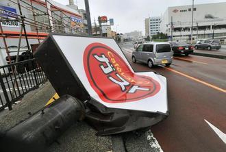 ファミリーレストランの看板が倒れ、国道58号にはみ出した=29日午後、浦添市牧港