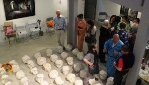沖縄の石を使った作品展「千と一の頭」をフランス各地で開いた井上さん(中央)=2012年12月、パリ3区の建築家組織本部