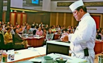参加者を前に、丁寧な手つきで盛りつけをする金城料理長=11日、沖縄かりゆしアーバンリゾート・ナハ