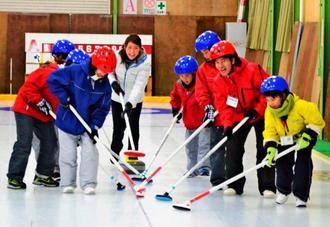 カーリング体験をする子供たち=1月30日、北海道南富良野町の「空知川スポーツリンクス」