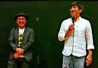 観客動員5万人突破を記念してあいさつする照屋年之さん(右)と山城智二さん=南風原町・サザンプレックス
