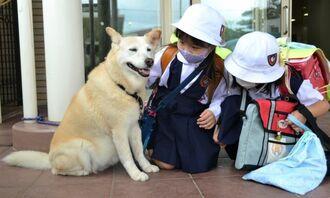 子どもたちに話しかけられて目を細めるハッピー(左)=7日、宜野湾市真栄原の沖縄カトリック小