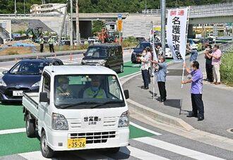 午前10時の開通と同時に名護東道路の世冨慶ICに入る地元住民ら=31日、名護市