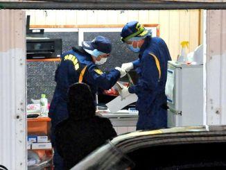 被害女性が倒れていた事務所内を調べる捜査員ら=5日午後8時10分ごろ、石垣市真栄里
