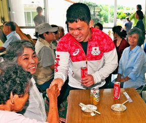 リオ五輪の重量挙げ男子62キロ級4位の入賞報告会で出身の久高島を訪ね、島民から握手を求められた糸数陽一さん(中央)=28日、南城市