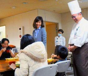 カレーを食べる子どもを笑顔で見つめる座間味良彦シェフ(右)や北條真奈巳社長(左から3人目)ら=10日、沖縄市住吉