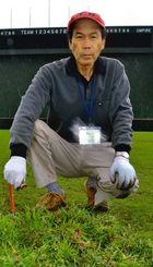2時間かけて抜き取った雑草を前にする奥間光吉さん=石垣市中央運動公園野球場