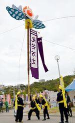 ヤクルトスワローズを歓迎する旗の前で演舞する伊祖旗頭保存会=1日、浦添運動公園