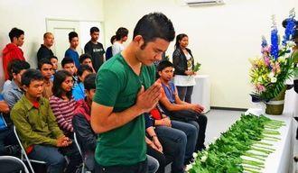 犠牲者へ献花をするネパール人の生徒たち=30日、那覇市・国際言語文化センター付属日本語学校