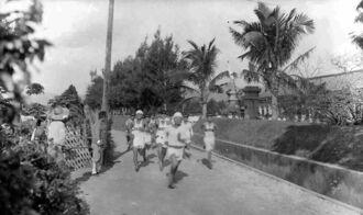 県立第三中学校の校門前を駆け抜ける生徒たち。校舎は現在の北部合同庁舎の敷地にあった。写真に写る門柱は現在の名護高校に現存している(「Urthman's Genealogy Blog」より)