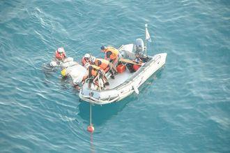 死亡した男性を引き上げる海上保安庁の職員=4日午前7時12分、伊良部大橋から