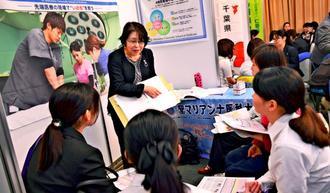 病院担当者の話を熱心に聞く学生ら=24日、宜野湾市のカルチャーリゾートフェストーネ