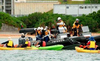 海保職員にボートに引き上げられる市民や、カヌーに乗って抗議する市民ら=30日午後12時8分、名護市辺野古沿岸(浦崎直己撮影)