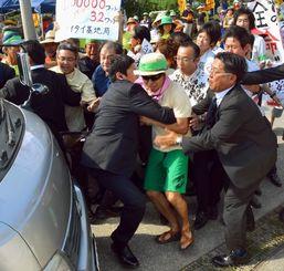 小野寺防衛相らが乗った車両に立ちふさがろうとして、警察官に取り押さえられる住民ら=19日午後、与那国町比川集落(新崎哲史撮影)