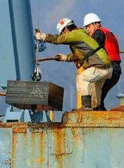 臨時制限区域を示すオイルフェンスを固定する鉄製のアンカーを撤去する作業員=13日午前9時34分、名護市・大浦湾(伊禮健撮影)