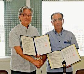 水道施設災害時の支援協定を結んだ県企業局の平良敏昭局長(右)と山田康夫会長=25日、県庁