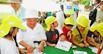 公園に置かれたテーブルで交流する地域のお年寄りや子どもたち=9日、那覇市曙・あけぼの公園