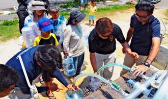 断水のため給水車から飲料用水を確保する住民=4月29日、伊良部中学校前の空き地