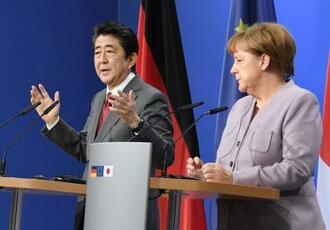 首脳会談を終え、ドイツのメルケル首相(右)と記者会見する安倍首相=20日、ドイツ・ハノーバー(共同)