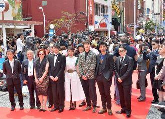 岡田将生さん(前列右から3人目)ら芸能人を一目見ようと多くの人が詰め掛けた国際通りのレッドカーペット=23日午後、那覇市牧志