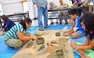 棒状にした粘土を積み上げ、土器の形にする参加者=22日、沖縄市青少年センター
