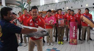 歓迎式で、読谷村漁業協同組合の金城肇組合長から30キロのキハダマグロを贈られる7人制ラグビー日本代表候補選手=2日午後1時すぎ、沖縄残波岬ロイヤルホテル