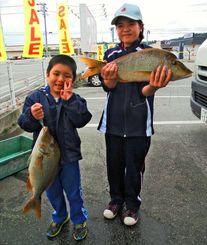 恩納村海岸で52センチ、1・84キロと53センチ、1・73キロのタマンを釣った平川聖龍さん(左)と未愛さん=20日