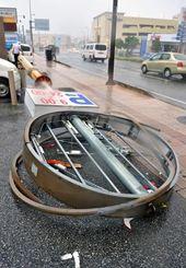 強風で鉄柱が折れ、倒れた店舗の看板=午後0時15分、浦添市牧港