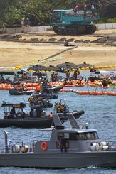 フロートをはさんで、新基地建設に反対するカヌー隊と海保がにらみ合う。浜辺ではトラックが石材を下ろす作業を進める=2017年4月25日、沖縄県名護市・米軍キャンプ・シュワブ沖