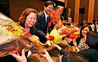 祝福に駆け付けた友人や教え子らから花束を受け取る受賞者(左側)=19日、那覇市の沖縄かりゆしアーバンリゾート・ナハ