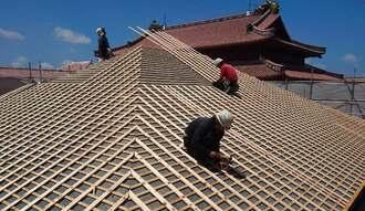 首里城の「女官居室」復元整備で作業する島袋瓦工場の社員。奥に見えるのは正殿の屋根=2016年5月27日(同工場提供)