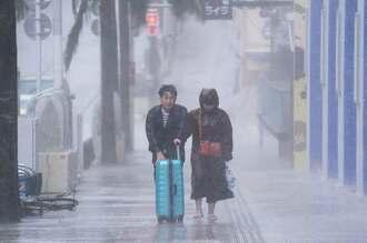 強い雨と風が吹き付ける中、歩く観光客=21日午前10時すぎ、那覇市牧志・国際通り