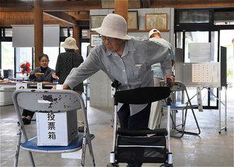 台風接近に伴う繰り上げ投票で1票を投じる有権者ら=27日午前8時40分、竹富町・竹富島まちなみ館