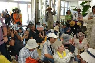 沖縄防衛局の玄関で座りこむ新基地建設に反対する市民ら=7日午前10時40分ごろ、嘉手納町・沖縄防衛局