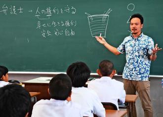 授業で「いじめは人権侵害。一生後悔する」と生徒に伝える横江崇弁護士=日、那覇市・寄宮中学校