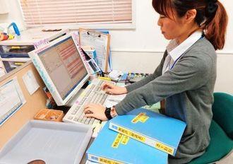 無料・低額診療患者の分納相談票などを整理する薬局員=那覇市古波蔵のこくら虹薬局